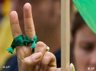 Hands wrapped in green clothe give peace sign