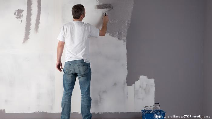 Man painting a wall in gray (picture-alliance/CTK Photo/R. Jansa)