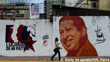A woman walks past a mural with an image of late Venezuelan president (1999-2013) Hugo Chavez in Caracas on August 22, 2018. - Confusion continues in Venezuela over new banknotes the government has put in circulation in an attempt to curb hyperinflation. (Photo by Federico PARRA / AFP) (Photo credit should read FEDERICO PARRA/AFP/Getty Images)