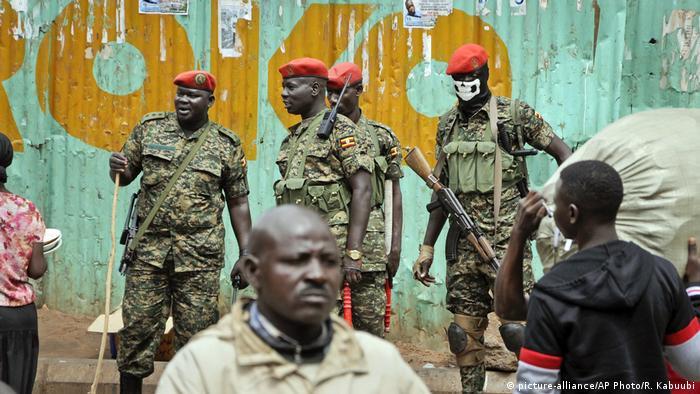 Ugandan soldiers look on as residents walk by.