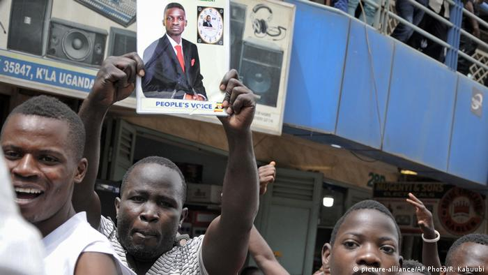 Bobi Wine supporters hold up a photo of him during demonstrations