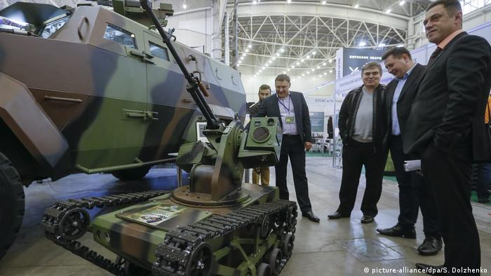 Visitors look at the Ukrainian-made combat robot 'Piranya' at the 'Arms and Security - 2016' exhibition in Kiev, Ukraine