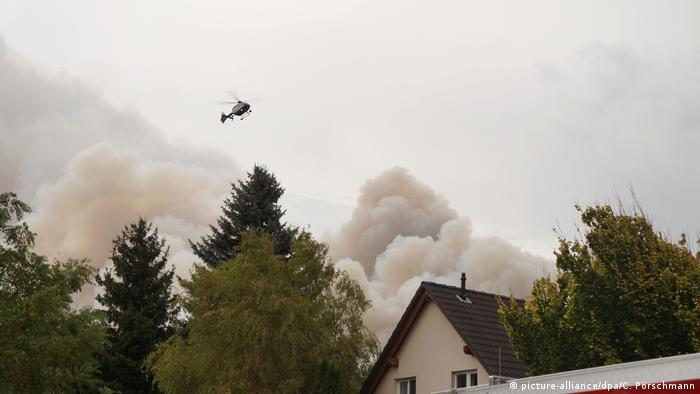 A helicopter flying above smoke from the fires (picture-alliance/dpa/C. Pörschmann)