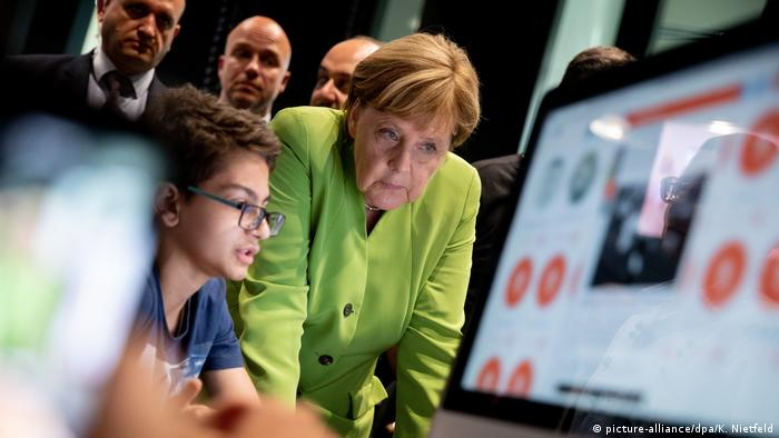 Angela Merkel with child in front of a computer (picture-alliance/dpa/K. Nietfeld)