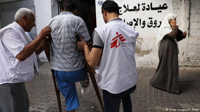 Two health workers support a man walking on crutches