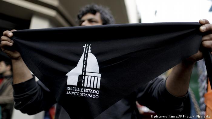 Vendedor oferece lenço com slogan pró Estado laico durante apostasia coletiva em Buenos Aires