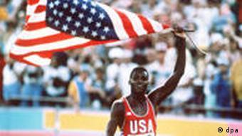 Der amerikanische Leichtathlet Carl Lewis bei einer Ehrenrunde,über dem Kopf schwenkt er eine große US-Flagge.
