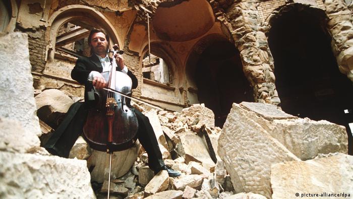 Cellist Vedran Smailovic in Ruine Nationalbibliothek von Sarajevo