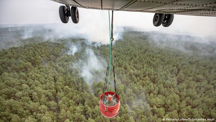 A military helicopter carries water over a forest