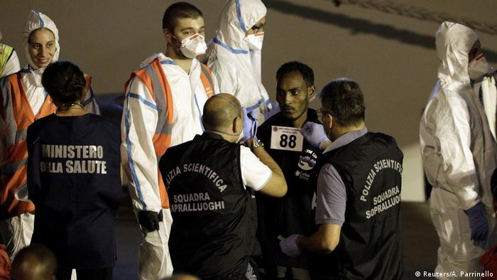 Migrant checked after disembarking boat