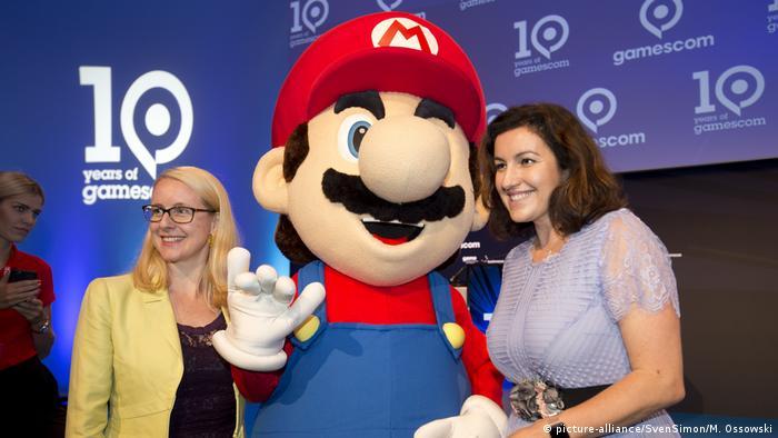 Dorothee Bär und ihre österreichische Amtskollegin Margarethe Schramböck mit einer überlebensgroßen Super-Mario-Figur bei der Messe Gamescom 2018.