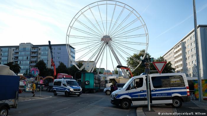 Машины полиции на фоне колеса обозрения в Хемнице