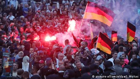 Right-wing demonstrators ignite pyrotechnics and wave German flags.