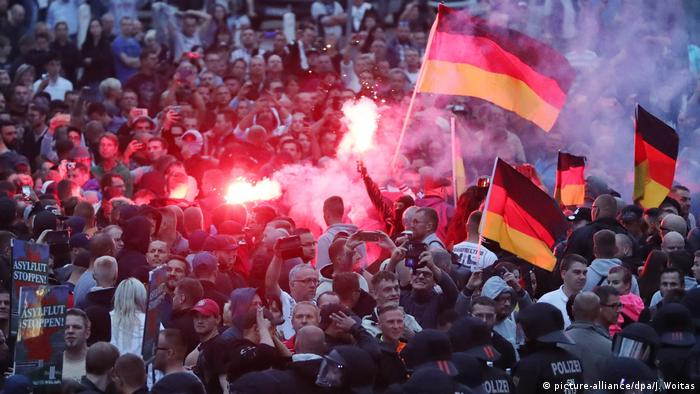 Demonstrators in Chemnitz hold up German flags and release flares during a right-wing protest against foreigners in Germany (picture-alliance/dpa/J. Woitas)