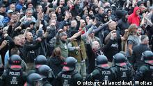 27.08.2018, Sachsen, Chemnitz: Polizisten stehen in der Innenstadt am Karl-Marx-Monument bei einer Kundgebung der rechten Szene, um ein Aufeinanderprallen von rechten und linken Gruppen zu verhindern. Nach einem Streit war in der Nacht zu Sonntag in der Innenstadt ein 35-jähriger Mann erstochen worden. Die Tat war Anlass für spontane Demonstrationen, bei denen es auch zu Jagdszenen und Gewaltausbrüchen kam. Foto: Jan Woitas/dpa   Verwendung weltweit