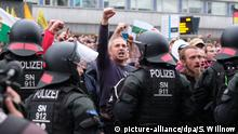 27.08.2018, Sachsen, Chemnitz: Rechte Demonstranten stehen vor dem Karl-Marx-Monument. Nach einem Streit war in der Nacht zu Sonntag den 26.08.2018 in Chemnitz ein 35-jähriger Mann erstochen worden. Die Tat war Anlass für spontane Demonstrationen, bei denen es auch zu Jagdszenen und Gewaltausbrüchen kam. Foto: Sebastian Willnow/dpa-Zentralbild/dpa +++ dpa-Bildfunk +++   Verwendung weltweit