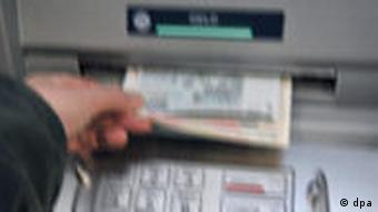 A person taking money out of an ATM