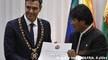 28.08.2018 Spanish Prime Minister Pedro Sanchez (L) is decorated by Bolivian President Evo Morales with the Order of the Condor of the Andes, Grand Collar, after signing bilateral agreements during a ceremony in Santa Cruz, Bolivia, on August 28, 2018. - Sanchez arrived in Bolivia on a two-day official visit. (Photo by Aizar RALDES / AFP) (Photo credit should read AIZAR RALDES/AFP/Getty Images)