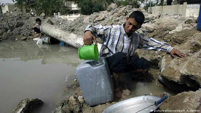 Boy pouring polluted water into canister (picture-alliance/dpa/O. Andersen)