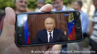 People watch on a smartphone screen as Vladimir Putin addresses the Russian public about the pension reform on state TV