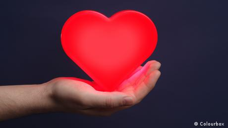 Man holding a red glowing heart on his palm
