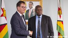 German development minister Gerd Müller shakes hands with Zimbabwe's former finance minister Patrick Chinamasa (Imago/photothek)