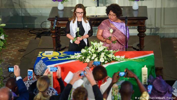 Staatsministerin Michelle Müntefering (links) und die namibische Kulturministerin Katrina Hanse-Hirmawa (rechts) stehen vor den menschlichen Gebeinen, die mit einer namibischen Flagge bedeckt sind