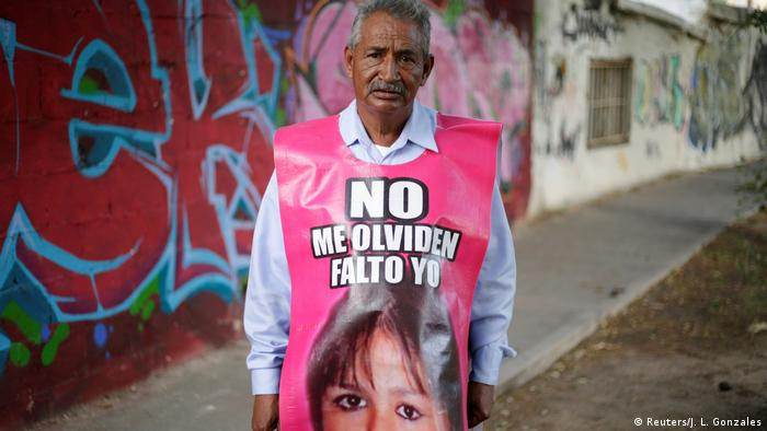 Jose Luis Castillo wearing a plastic banner with a photo of his missing daughter