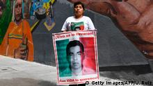 Mexican Cristina Bautista, mother of Benjamin Ascencio Bautista -one of the 43 missing students missing of Ayotzinapa-, holds his portrait as she poses for a photograph in Mexico City on June 26, 2018. - Bautista gave her take ahead of the country's July 1 presidential election. (Photo by Ulises RUIZ / AFP) (Photo credit should read ULISES RUIZ/AFP/Getty Images)