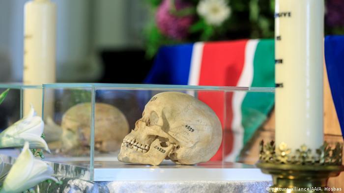 Zwei Schädel in einer Glasvitrine, daneben zwei Kerzen und im Hintergrund die namibische Flagge