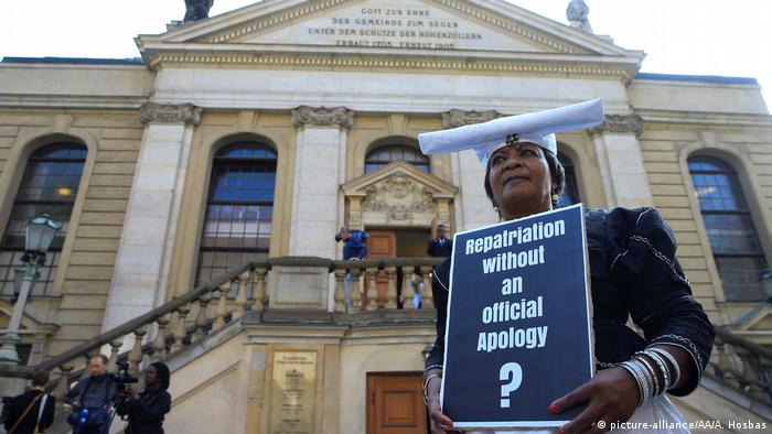 A woman wearing a traditional Herero head covering holds a placard that reads: Reparations without an official Apology?