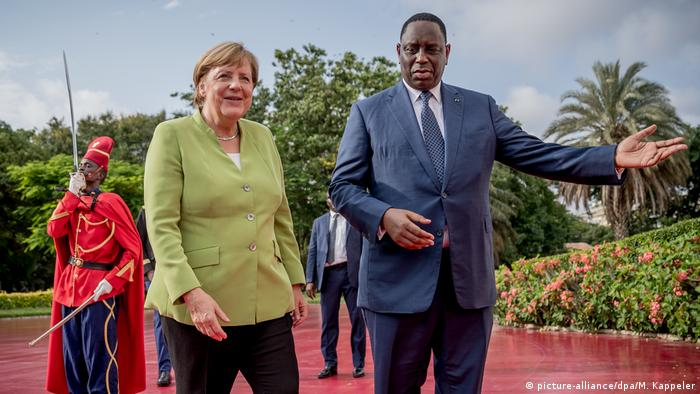 German Chancellor Angela Merkel receiving a red carpet welcome from President Macky Sall on a visit to Senegal