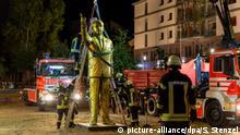 dpatopbilder - 28.08.2018, Hessen, Wiesbaden: Feuerwehrleute heben eine Statue des türkischen Staatspräsidenten Recep Tayyip Erdogan mit Hilfe eines Krans von einem Platz. Die Stadt Wiesbaden hat entschieden, die als Teil eines Kunstfestivals aufgestellte Statue des türkischen Staatspräsidenten Recep Tayyip Erdogan abbauen zu lassen. Die Kunstinstallation im Rahmen der Wiesbaden Biennale hatte viel Aufsehen erregt und für Irritationen gesorgt. Die Sicherheit habe nicht mehr gewährleistet werden können, teilte die Stadt am späten Dienstagabend den 28.08.2018 über Twitter mit. Die Räumung des Platzes, auf dem die rund vier Meter hohe und goldfarbene Statue seit Montag stand, war nach Polizeiangaben ohne besondere Vorkommnisse verlaufen. Foto: Sebastian Stenzel/Wiesbaden112.de/dpa   Verwendung weltweit