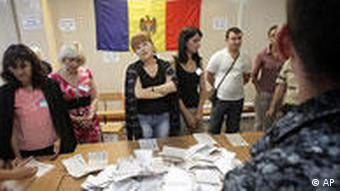 Election officials count votes under a Moldovan flag after polls closed in Chisinau