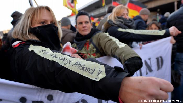 An archive photo showing a PEGIDA demonstration in Cologne, Germany, on 09.01.2016. Several women in the foreground are displaying a slogan on their sleeves, the message roughly translates as keep at arm's length. The protest followed the New Year's Eve assaults on women in the center of Cologne that year.