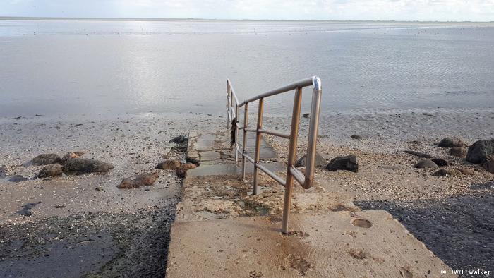 Ein Geländer führt ins Wasser an einem Strand an der Nordsee