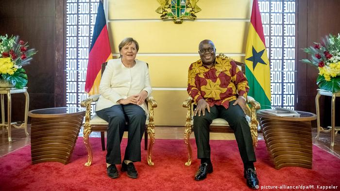 Germany's Chancellor Angela Merkel and Ghanaian president Akufo-Addo seated in front of the flags of their respective countries