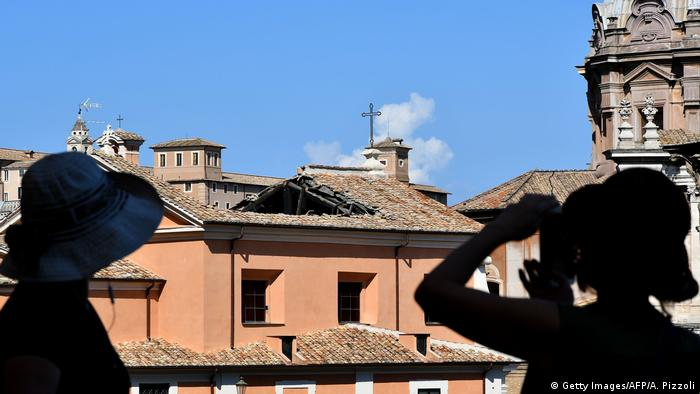Bystanders look on at the collapsed roof of the Chiesa di San Giuseppe dei Falegnami (Getty Images/AFP/A. Pizzoli)