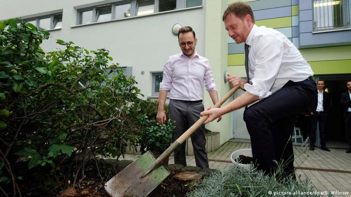 Michael Kretschmer plants a rosebush (picture-alliance/dpa/S. Willnow)