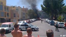 Tourists look at the smoke and flames coming from a car explosion in the Palmanova beach area, southwest of the island's capital, Palma de Mallorca, Spain, Thursday, July 30, 2009. An explosion on the Spanish resort island of Mallorca killed two police officers Thursday and authorities blocked all outgoing flights and ships from leaving as part of a manhunt. The bombing, blamed on Basque separatist group ETA, targeted a police vehicle. It was the second attack linked to ETA in less than 36 hours. A powerful car bomb Wednesday destroyed a police barracks in the northern Spanish city of Burgos, injuring about 60 people. (AP Photo)