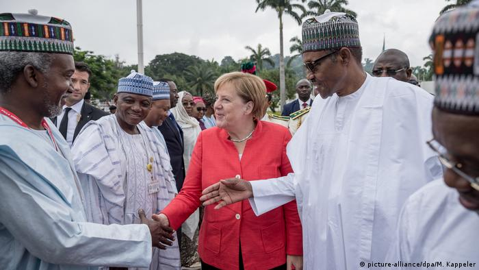 German Chancellor Angela Merkel stands alongside Nigerian President Muhammadu Buhari during her visit to Nigeria (picture-alliance/dpa/M. Kappeler)