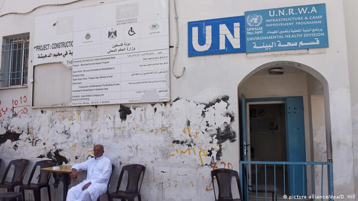 A Palestinian refugee sits outside a UNRWA building in Bethlehem, West Bank. (picture-alliance/dpa/D. Hill)