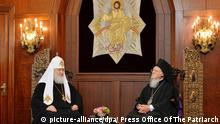 Patriarch Kirill und Patriarch Bartholomew sit across from one another under an image of Jesus Christ (picture-alliance/dpa/ Press Office Of The Patriarch)