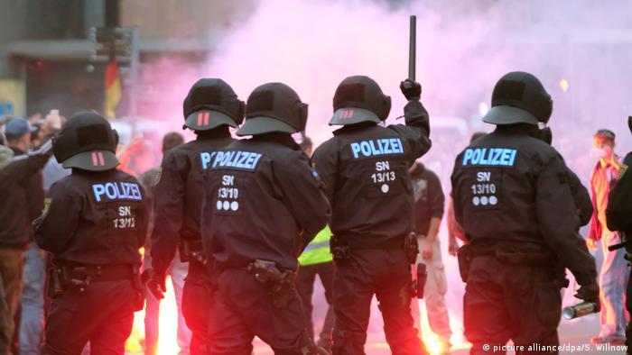Policiais de batalhão de choque alemão, vistos por trás, com capacete, roupa preta e com cassetetes