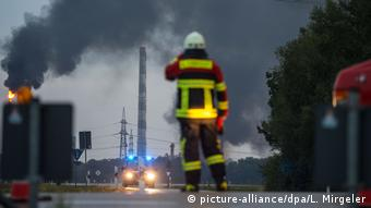 Firefighter watching the smoke rising from the refinery (picture-alliance/dpa/L. Mirgeler)