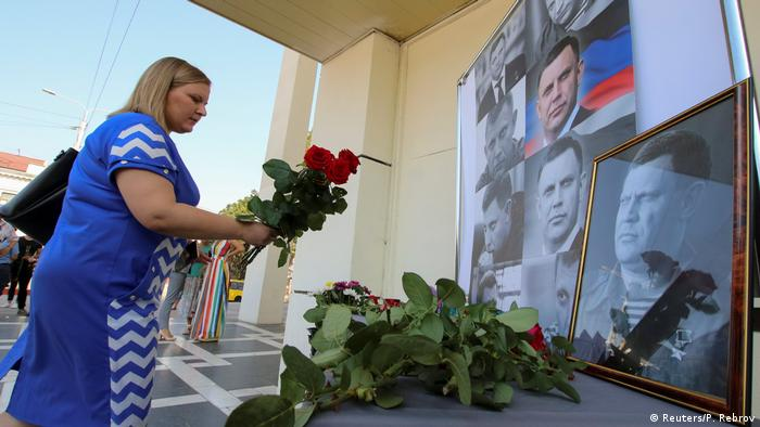A woman places flowers in front pictures of the leader of the separatist self-proclaimed Donetsk People's Republic, Alexander Zakharchenko