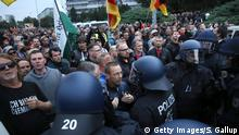 CHEMNITZ, GERMANY - SEPTEMBER 01: Participants in a right-wing march confront riot police after police halted the march due to a blockade by counter-demonstrators on September 1, 2018 in Chemnitz, Germany. Several thousand people had taken part in a march of silence organized by the right-wing Alternative for Germany (AfD) political party. Two refugees, a Syrian and an Iraqi, are accused of having stabbed Chemnitz local Daniel Hillig following an altercation in the early hours of August 26. The death has sparked angry protests by locals as well as right-wing groups that have led to clashes with police and counter-protesters. (Photo by Sean Gallup/Getty Images)