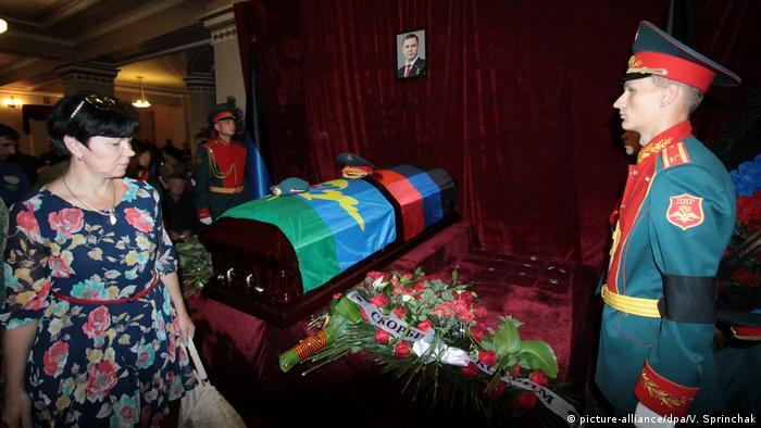 A woman stands before Ukrainian separatist leader Alexander Zakharchenko's casket in Donetsk