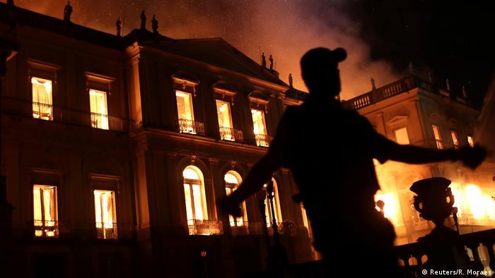 Policial evacua área à frente do Museu Nacional durante incêndio da instituição, no dia 2 de setembro de 2018. Prédio do museu aparece ao fundo, em chamas
