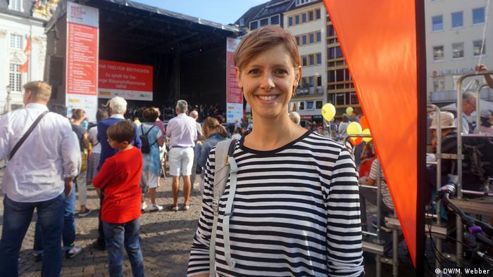 Frau mit schwarzweiß gestreiftem Hemd lächelt vor der Bühne. Beethoven-Fest Bonn 2018 (DW/M. Webber)